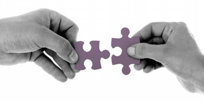 Two hands joining together puzzle pieces