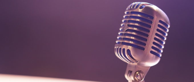 Closeup on an old style silver microphone with a purple background